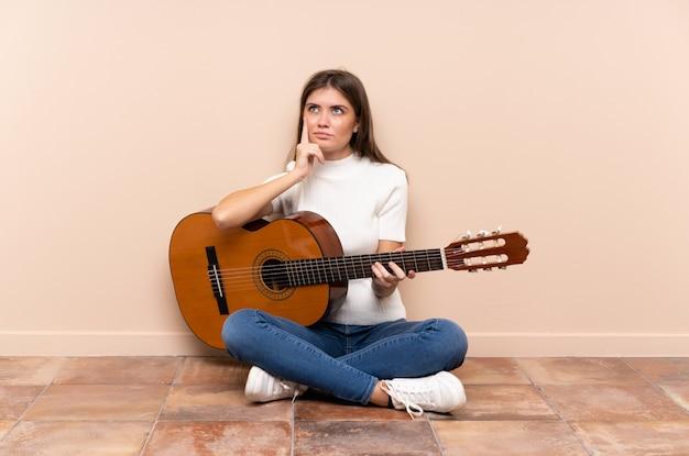 Młoda kobieta z gitarą siedzi na podłodze myśląc pomysł