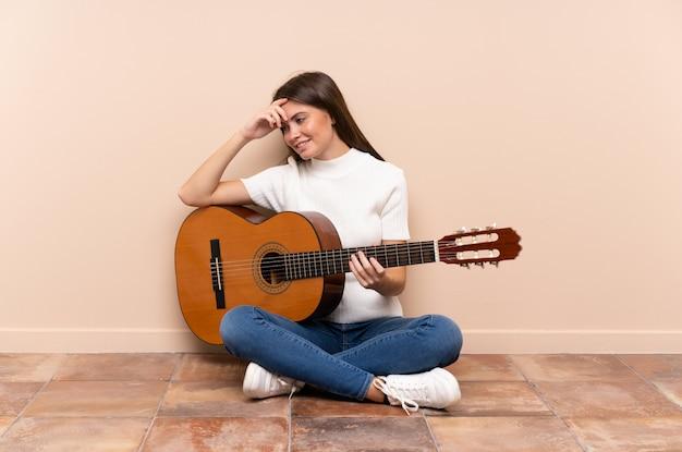 Młoda kobieta z gitarą siedzi na podłodze śmiejąc się
