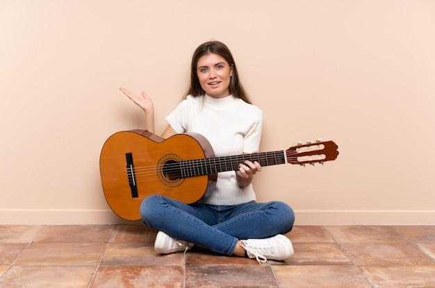Młoda kobieta z gitary obsiadaniem na podłoga trzyma copyspace imaginacyjnego na palmie