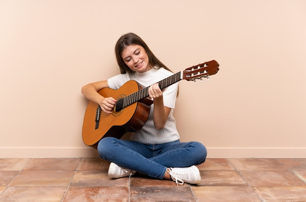 Młoda kobieta z gitary obsiadaniem na podłoga