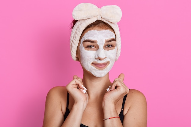 Młoda kobieta z glinianą maską na twarzy pozuje na różowej ścianie, wesoła dziewczyna wykonuje zabiegi pielęgnacyjne w domu, jest w dobrym nastroju, trzymając pięści przy twarzy.