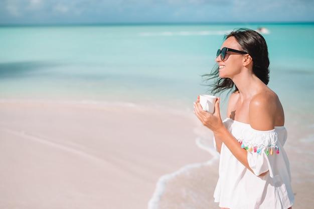 Młoda kobieta z gorącą kawą cieszy się plażowego widok