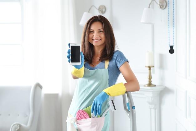 Młoda kobieta z gumowymi rękawiczkami pokazuje smartfon