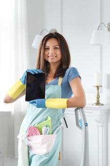 Młoda kobieta z gumowymi rękawiczkami pokazuje tablet