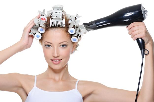 Młoda kobieta z hair-curles i suszarką do włosów robi fryzurę na białym tle