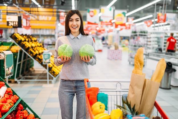 Młoda kobieta z huśtawkami kapusta w supermarkecie