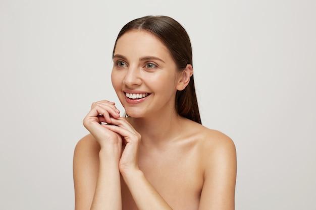Młoda kobieta z idealnie zdrową, świeżą skórą wygląda na bok, uśmiechając się