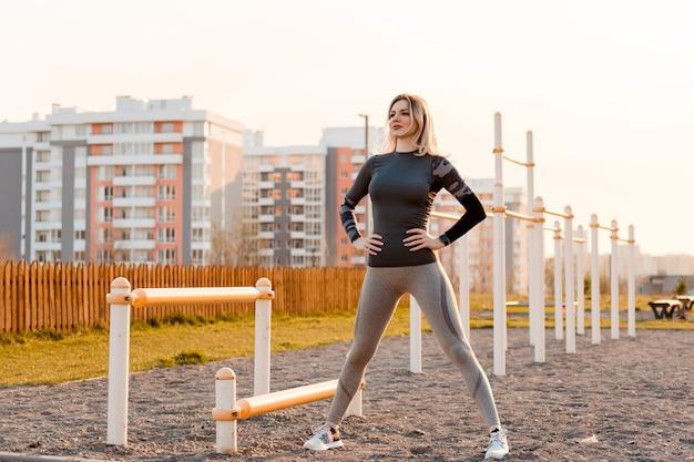 Młoda kobieta z idealnym ciałem w sportowej pociągi na zewnątrz na placu zabaw. koncepcja zdrowego stylu życia, sportu i ćwiczeń.