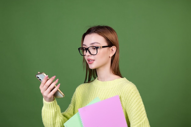 Młoda kobieta z idealnym naturalnym makijażem brązowe duże usta w swobodnym swetrze na zielonej ścianie uczeń w okularach i zeszytach trzymających telefon komórkowy