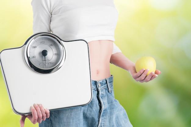 Młoda kobieta z jabłkiem i wagami. zdrowa dieta i odchudzanie