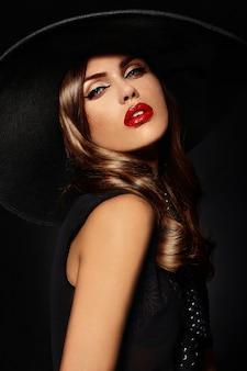 Młoda kobieta z jasny makijaż i czarny kapelusz