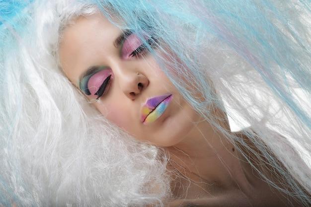 Młoda kobieta z jasny makijaż i kreatywne włosy