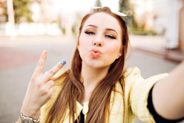 Młoda kobieta z jasny makijaż mrówkowy blond włosy sprawia, że selfie wysyłając pocałunek, hipster uliczny portret. pokazuje znak pokoju, robiąc sobie zdjęcia.