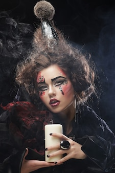 Młoda kobieta z jasny makijaż na sobie kostium karnawałowy trzyma świecę. zdjęcie halloween.
