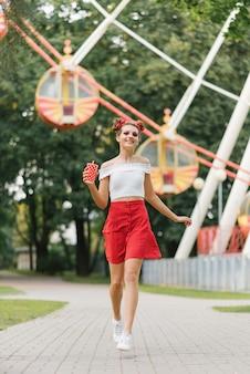 Młoda kobieta z jasnym makijażem trzyma w dłoniach czerwony papierowy kubek i biegnie przez park rozrywki. jest uśmiechnięta i szczęśliwa.