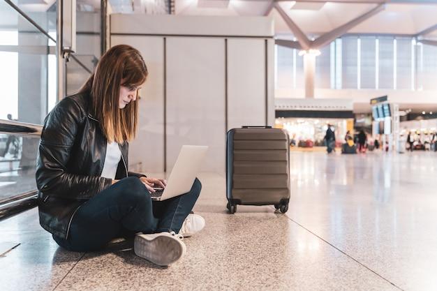 Młoda kobieta z jej bagażem i jej laptopu czekaniem przy lotniskiem. pojęcie podróży i wakacji.