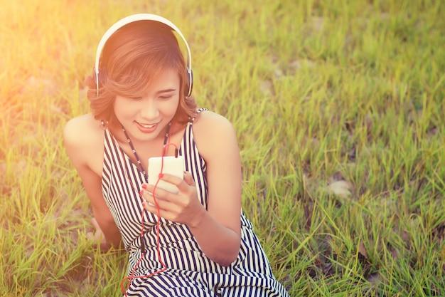 Młoda kobieta z jej telefon komórkowy siedzi na trawie