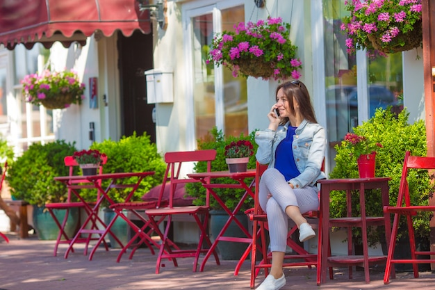 Młoda kobieta z jej telefonem przy plenerową kawiarnią w europejskim mieście