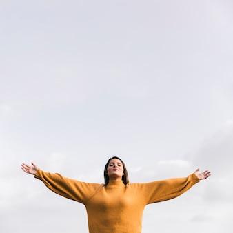 Młoda kobieta z jej zamkniętymi oczami szeroko rozpościerać ręki stoi przeciw niebu