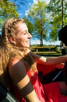 Młoda kobieta z kabrioletem w lecie na jednodniowej wycieczce