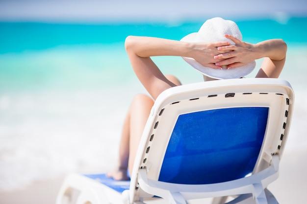Młoda kobieta z kapeluszem na lounger przy tropikalną plażą