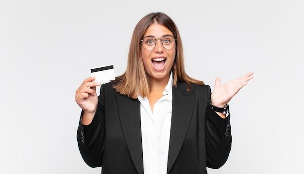 Młoda kobieta z kartą kredytową czuje się szczęśliwa, podekscytowana, zaskoczona lub zszokowana, uśmiechnięta i zdumiona czymś niewiarygodnym