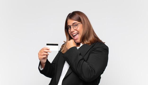 Młoda kobieta z kartą kredytową czuje się szczęśliwa, pozytywna i odnosząca sukcesy, zmotywowana, gdy staje przed wyzwaniem lub świętuje dobre wyniki