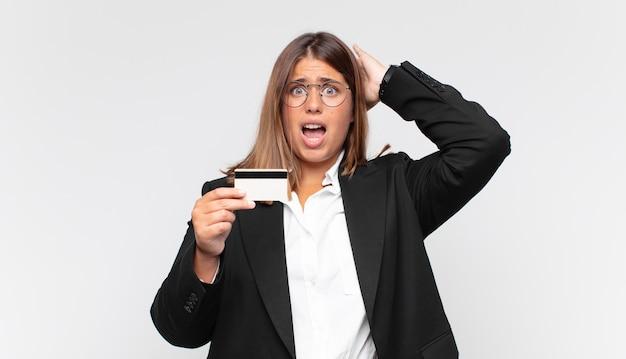 Młoda kobieta z kartą kredytową czuje się zestresowana, zmartwiona, niespokojna lub przestraszona, z rękami na głowie, panikuje podczas pomyłki
