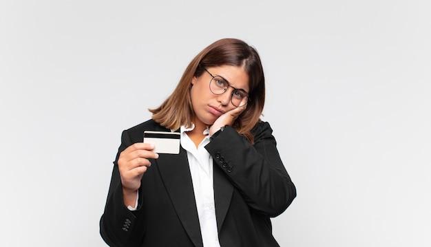 Młoda kobieta z kartą kredytową czuje się znudzona, sfrustrowana i senna po męczącym, nudnym i żmudnym zadaniu, trzymając twarz ręką