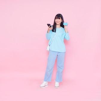 Młoda kobieta z kartą kredytową i smartfonem na różowej ścianie. zakupy online