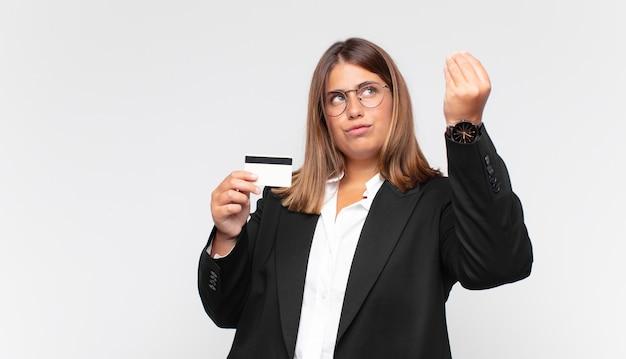 Młoda kobieta z kartą kredytową robi gest kaprysu lub pieniędzy i każe ci spłacić swoje długi!