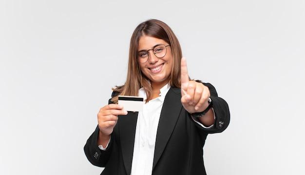 Młoda kobieta z kartą kredytową, uśmiechnięta i przyjazna, pokazująca numer jeden lub pierwszy z ręką do przodu, odliczająca w dół
