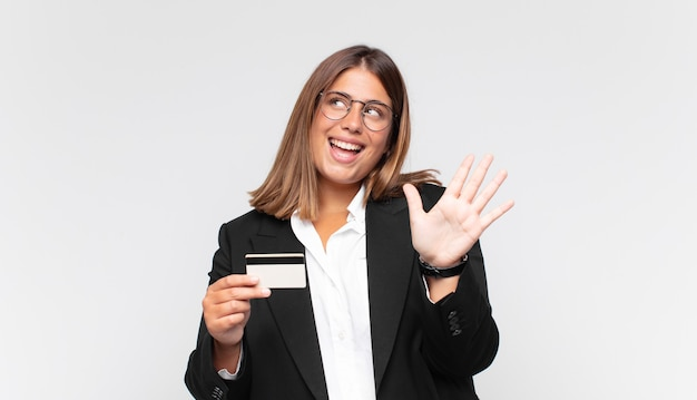 Młoda kobieta z kartą kredytową, uśmiechnięta i wyglądająca przyjaźnie, pokazująca numer pięć lub piąty z ręką do przodu, odliczający w dół