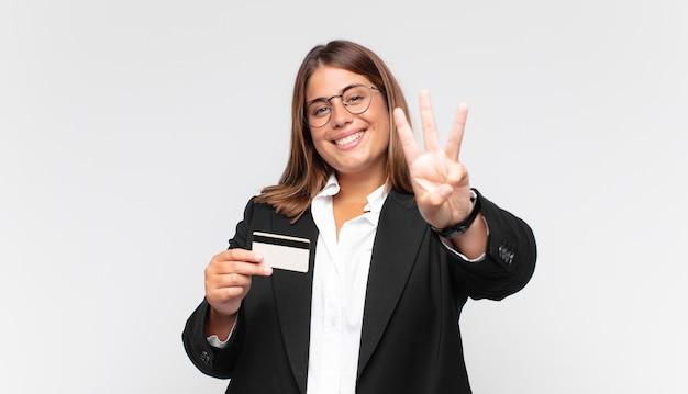 Młoda kobieta z kartą kredytową, uśmiechnięta i wyglądająca przyjaźnie, pokazująca numer trzy lub trzeci z ręką do przodu, odliczający w dół