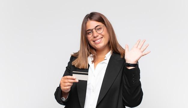 Młoda kobieta z kartą kredytową, uśmiechnięta radośnie i wesoło, machająca ręką, witająca i witająca lub żegnająca się
