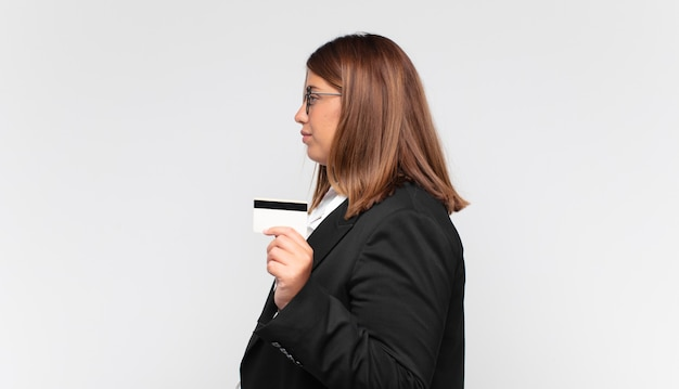 Młoda kobieta z kartą kredytową w widoku profilu, która chce skopiować przestrzeń do przodu, myśląc, wyobrażając sobie lub marząc