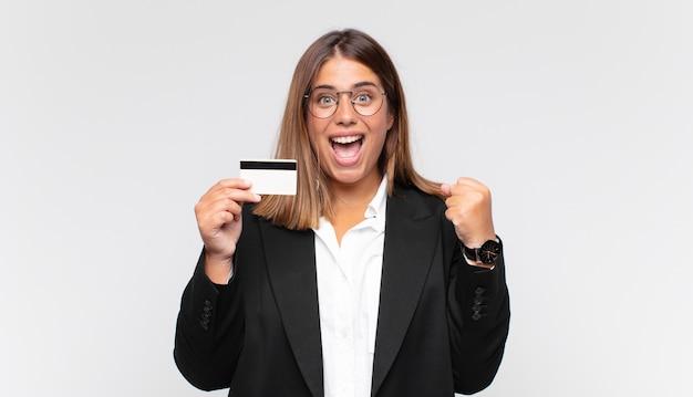 Młoda kobieta z kartą kredytową, zszokowana, podekscytowana i szczęśliwa, śmiejąca się i świętująca sukces, mówiąca wow!