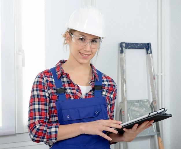 Młoda kobieta z kask ochronny, za pomocą cyfrowego tabletu