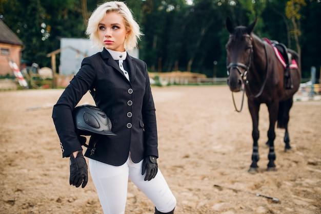 Młoda kobieta z kaskiem w ręce pozuje przeciwko koniu, jazda konna. ogier brązowy, wypoczynek ze zwierzętami, sport jeździecki