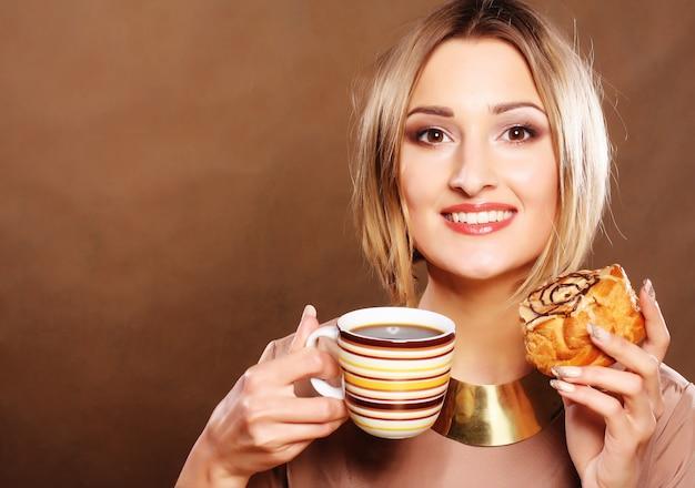 Młoda kobieta z kawą i ciastkami.