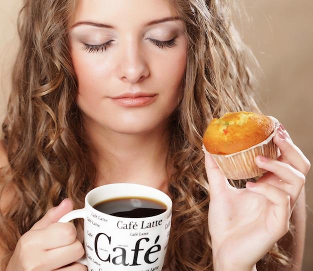 Młoda kobieta z kawą i słodka bułeczka