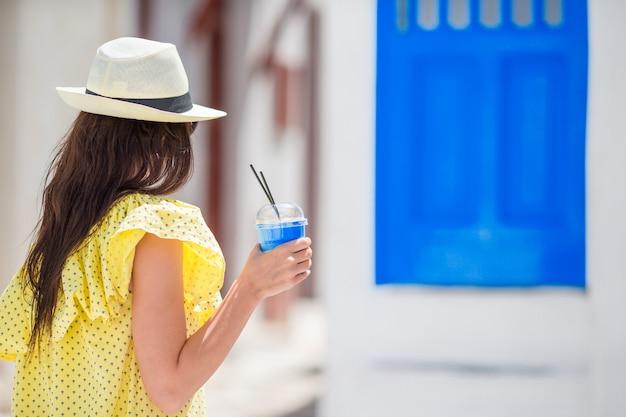 Młoda kobieta z kawą iść wąskimi uliczkami starej greckiej wioski w grecja