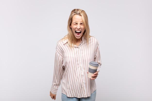 Młoda kobieta z kawą krzycząca agresywnie, wyglądająca na bardzo wściekłą, sfrustrowaną, oburzoną lub zirytowaną, krzycząca nie