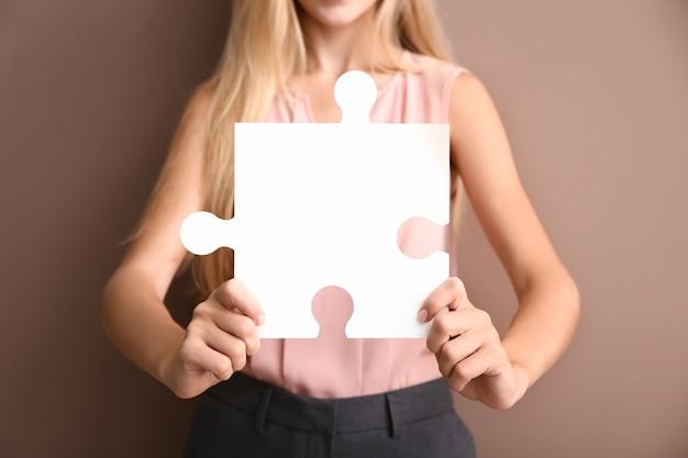 Młoda kobieta z kawałkiem układanki na kolor