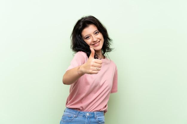 Młoda kobieta z kciukami do góry, ponieważ stało się coś dobrego