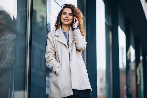 Młoda kobieta z kędzierzawym włosy używać telefon przy ulicą
