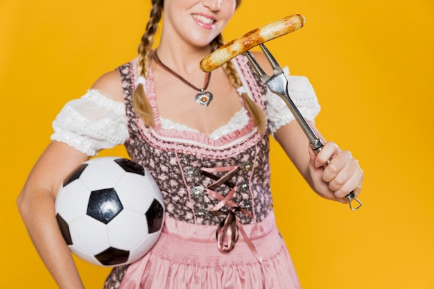 Młoda kobieta z kiełbasą i piłką