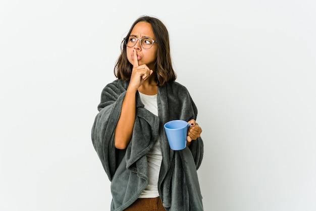 Młoda kobieta z kocem na białym tle na białej ścianie, zachowując tajemnicę lub prosząc o ciszę