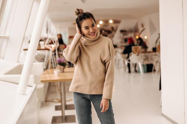 Młoda kobieta z kok i ubrana w beżowy sweter i ciemne spodnie jeansowe pozowanie w kawiarni