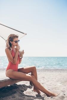 Młoda kobieta z koktajlu szkłem na biel plaży obsiadaniu na sunbed
